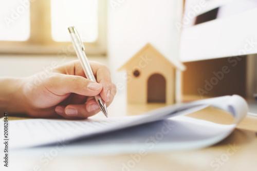 Zdjęcie XXL Bliska ręka człowieka podpisania dokumentu pożyczki do własności domu. Inwestycje hipoteczne i nieruchomościowe