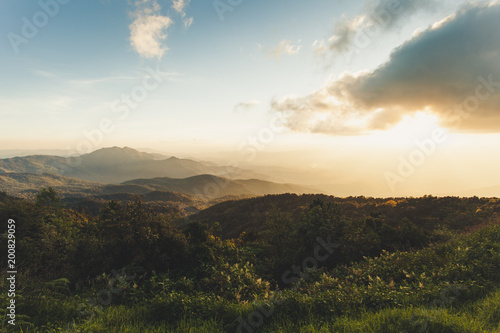 Tuinposter Beige Smoky mountain landscape with mountain and light rays in sunset scene.