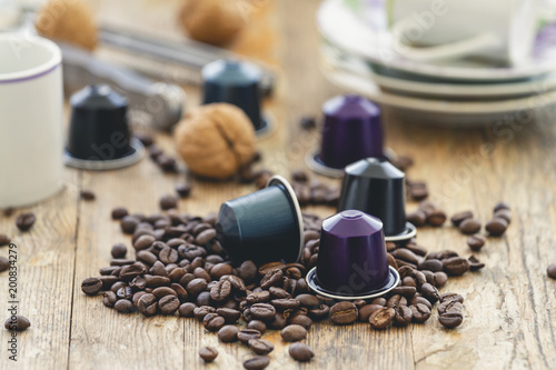 Italian espresso coffee capsules or coffee pods with espresso cups and coffee beans on a rustic wood background. Coffee accessories composition