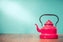 Retro Classic Red Kettle On Oak Wooden Table In Front Mint Green Background. Old Style Filtered Photo
