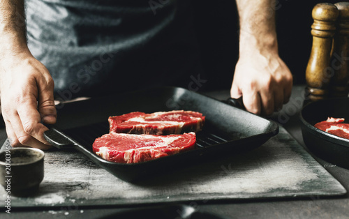 Poster Cuisine Male hands holding grill pan with raw beef steak