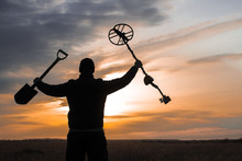 Treasure Hunter With A Metal Detector On A Beveled Wheat Field In Search Of Adventure Against The Backlight Of The Sun