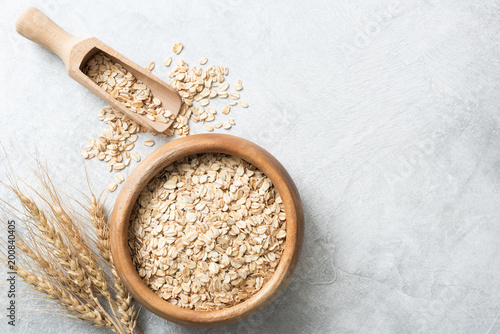 Poster Graine, aromate Organic rolled oats in wooden bowl on concrete background. Top view with copy space for text. Concept of healthy lifestyle, healthy eating, dieting, sport and fitness menu