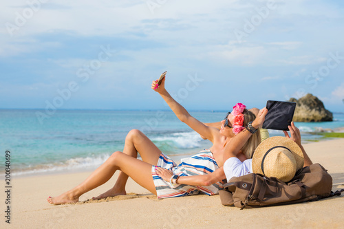 Papiers peints Statue Couple relaxing on the beach and using tech devices
