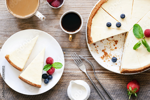 Homemade classical New York cheesecake and coffee on wooden table. Top view