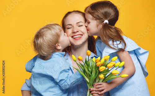 concept of mother's day. mom and children with flower on colored background