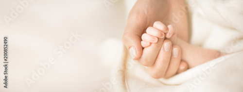 Fototapeta Female hand holding her newborn baby's hand. Mom with her child. Maternity, family, birth concept. Copy space for your text. Banner obraz