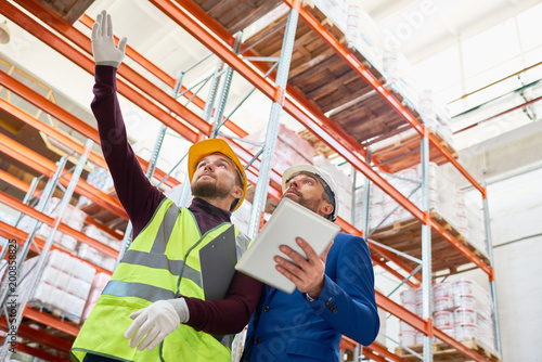 Foto Low angle portrait of warehouse manager holding clipboard talking to worker wear