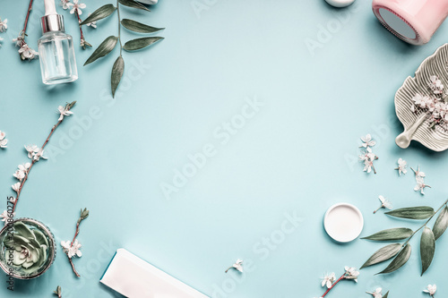 Fotografía  Facial cosmetic products, leaves and cherry blossom on blue table