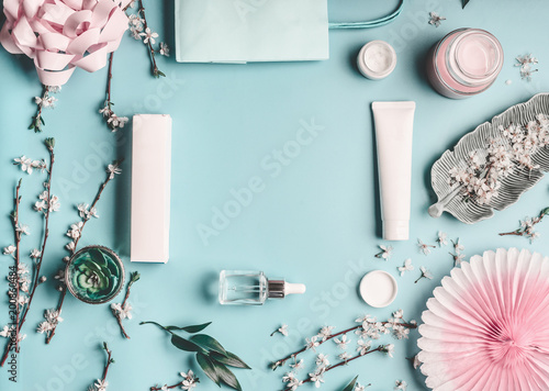 Central Europe Beauty concept with facial cosmetic products, shopping bag and twigs with cherry blossom on pastel blue desktop background. Modern spring skin care trends, top view, frame, flat lay. Branding mock up
