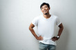 Young asian guy in white blank t-shirt, grunge wall, studio portrait