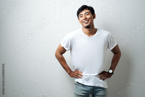 Foto  Young asian guy in white blank t-shirt, grunge wall, studio portrait