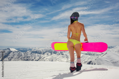 Fotografía  Back view of a slim and sexy girl in swimsuit and helmet holding a snowboard