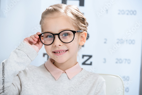 adorable smiling child looking at camera in glasses at oculist consulting room Wallpaper Mural