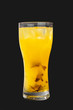 A single-colored yellow opaque cocktail, cold tea in a tall glass with ice cubes with the taste of pineapple, orange. Side view. Isolated black background. Drink for the menu restaurant, bar, cafe