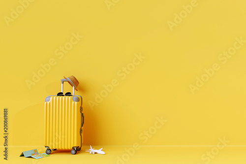 Yellow suitcase with sun glasses and hat on yellow background Fototapeta