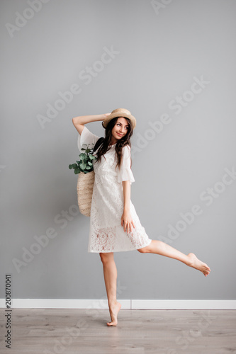 29ddb48a beautiful young brunette girl in white short dress, wearing hat, with summer  bag in hand on gray background. Let's go shopping
