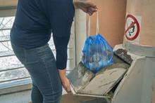 Woman Puts A Garbage Bag In A Lid Of Home Garbage Chute