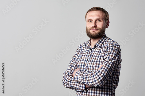 Fotografiet  Portrait of serious bearded man in checkered shirt standing on gray background w