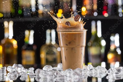 Obraz na plátně Cold coffee drink with ice, beans and splash.