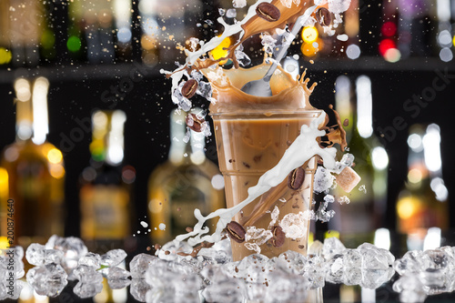 Fototapeta  Cold coffee drink with ice, beans and splash.