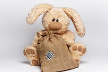 Soft Toy Rabbit Sits With A Bag On A White Background.