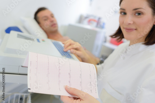 Fotografía  Woman looking at heart monitor printout