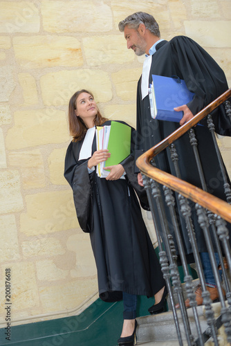 Foto  Male and female magistrates walking down stairs