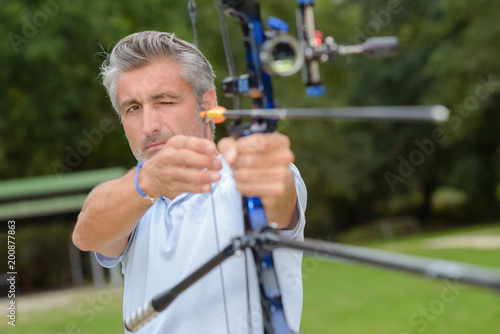 Photographie Man aiming archery bow