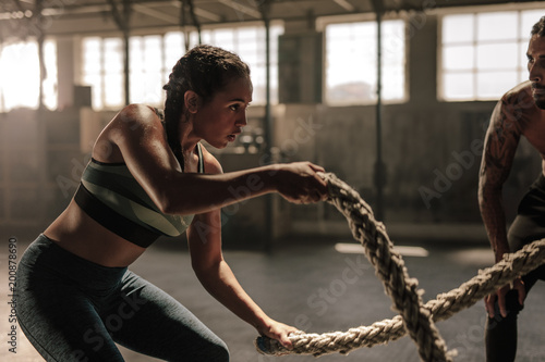 La pose en embrasure Fitness Woman doing battle rope workout at gym