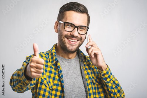 Happy handsome man showing thumbs up on the grey background. Using phone.