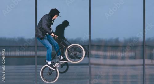 BMX freestyle. Stylish man doing tricks on BMX against a dark shop window. Street culture