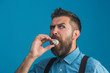 Fresh idea! Surprised bearded man in denim shirt and suspenders holds light bulb in his mouth. Young man with beard and mustache holds light bulb in her mouth. Businessman creating ideas. Copy space.