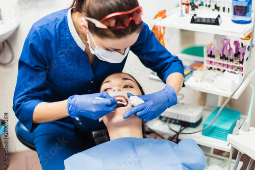 Fotografia  Dentist holding tooth whitening procedure
