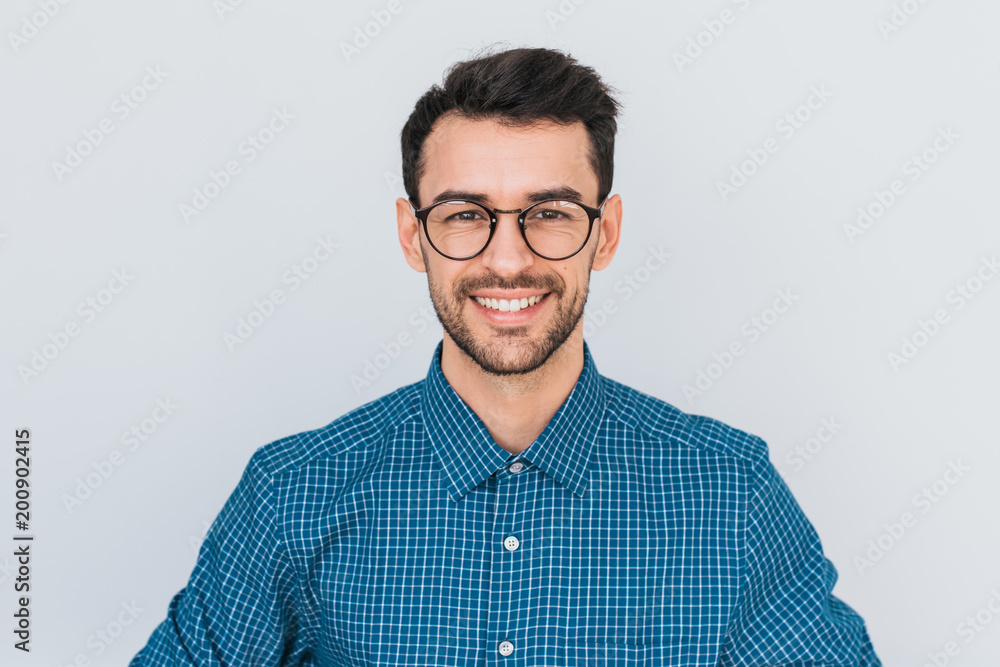 Fototapeta Closeup portrait of handsome smart-looking smiling with toothy smile male posing for social advertisement, isolated on white background with copy space for your promotional information or content.