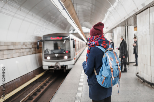 woman traveler with backpack waiting for train in subway station