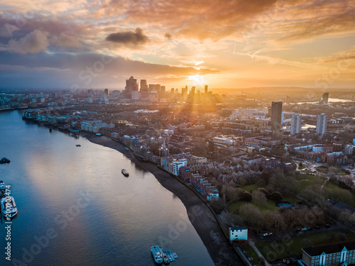 Foto auf Leinwand Luftaufnahme London, England - Panoramic aerial skyline view of east London at sunrise with skycrapers of Canary Wharf and beutiful colorful sky at background
