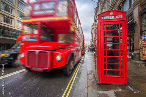 Foto auf AluDibond London roten bus London, England - Iconic blurred black londoner taxi and vintage red double-decker bus on the move with traditional red telephone box in the center of London at daytime