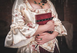 Woman in old historic medieval dress with book