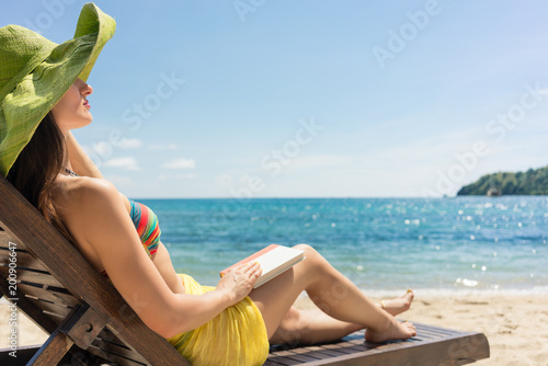 Groovy Side View Of A Young Beautiful Woman Reading A Book While Ocoug Best Dining Table And Chair Ideas Images Ocougorg