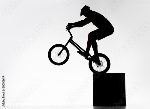 Photo silhouette of trial cyclist performing back wheel stand while balancing on cube