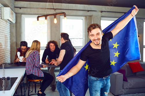 Foto  Young man with the european flag in his hands on the background of friends in the room