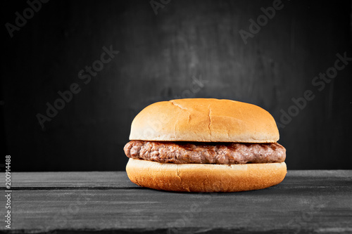 Plain beef burger on wooden table isolated on black background Canvas Print