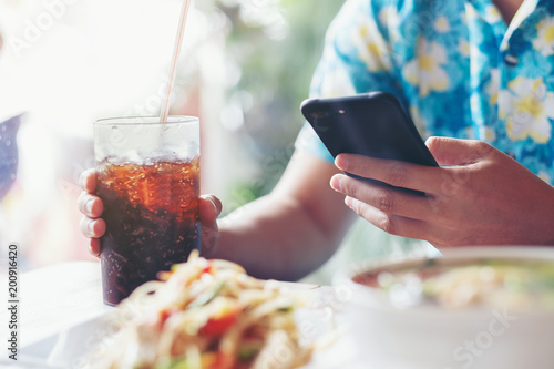 Men play smartphone and hand hold of glass soft drink in cafe restaurant wait food
