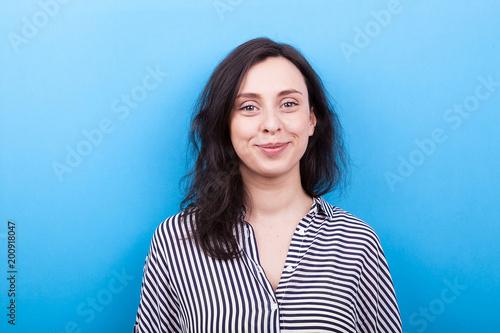 Fotografie, Obraz  Smiling girl on blue background in studio photo