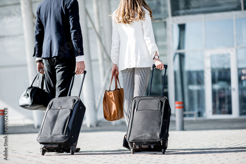 Other Business couple walking together to the airport entrance carrying suitcases and bags