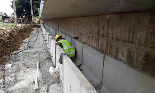 Fotografija  Construction workers installing precast concrete drain at the construction site