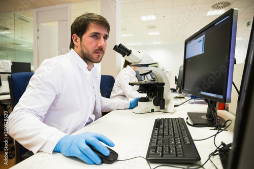 Handsome man in lab coat using computer and microscope while working ininnovative laboratory.