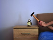Image Shows Hands Holding A Hammer Trying To Smash An Alarm Clock.