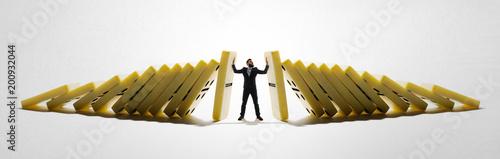 Fototapeta The man stops the falling dominoes. Concept of crisis management. obraz